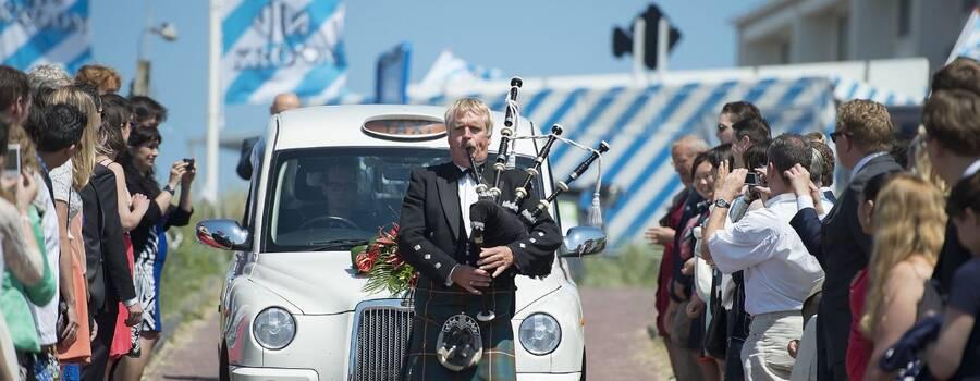 Aankomst van het bruidpaar bij de trouwlocatie op een indrukwekkende en onvergetelijke manier in de witte Engelse taxi en  vooraf gegaan door mij als Schotse doedelzakspeler.