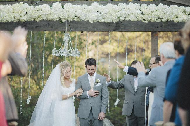 Ceremonia chic con flores y lámpara colgante.