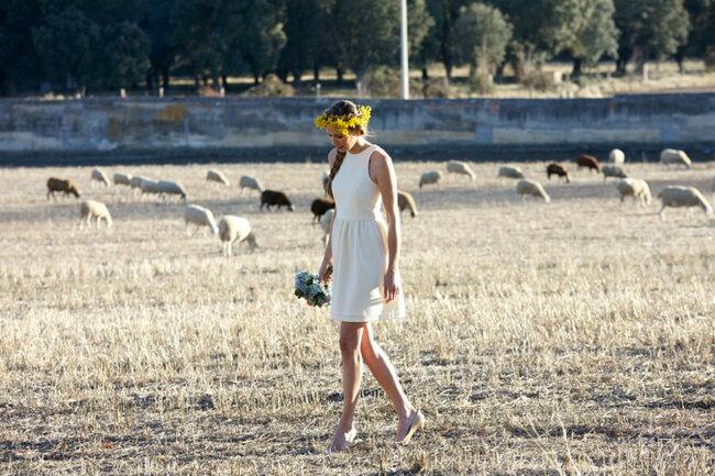 Ana porte une mini robe de mariée avec une jupe volante ainsi qu'une couronne de fleurs jaunes.