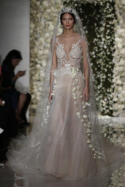 Vestido de novia con cientos de aplicaciones, falda de gasa con toques de color marfil, cuello pronunciado y cauda larga