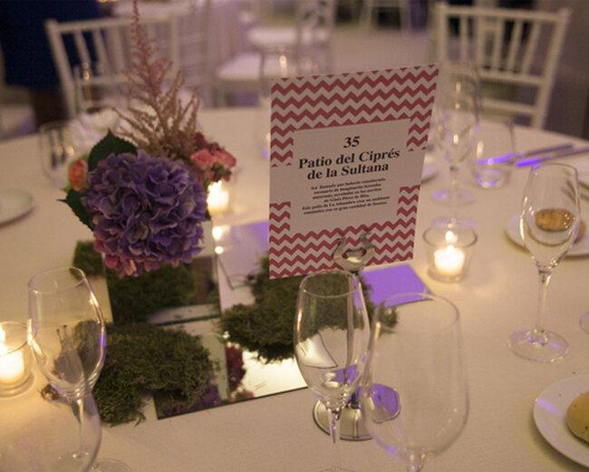 Detalle de centro de mesa con flores, velas y marca sitios personalizado