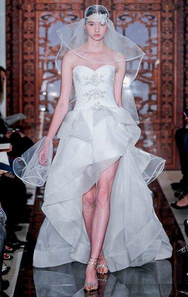 Vestido de novia con escote strapless, acabado asimétrico y brocados en el corpiño