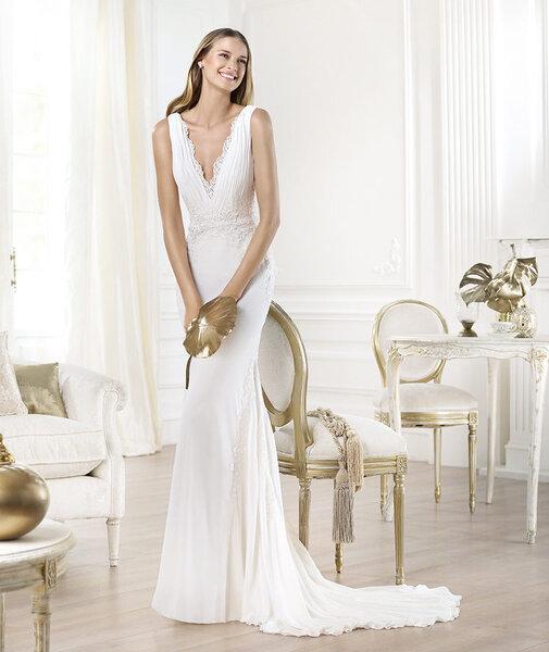 Vestido de novia con detalles de encaje en el escote y cauda barrida