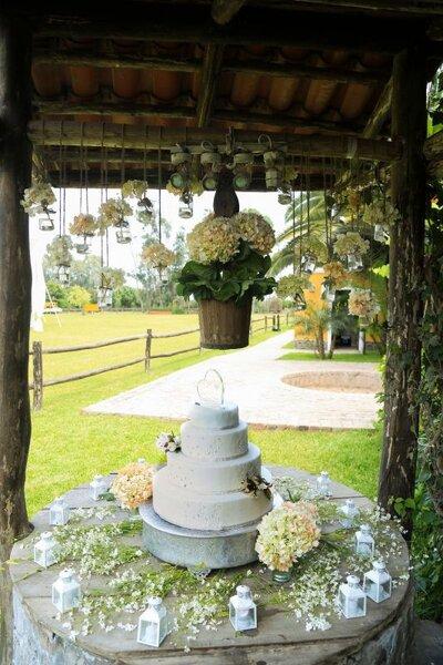 Un acabado de ensueño para bodas al aire libre, las cubetas de madera sostienen a las flores y la mesa de la torta encanta con sus pequeños faroles y flores silvestres.