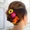 Kwiaty ogrodowe we włosach panny młodej.