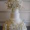 Pastel de bodas en color blanco con cuatro pisos y con adornos de flores