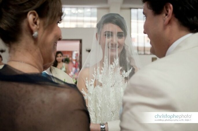 La novia aun con su velo sobre el rostro, alegre por el momento más especial de su vida. Foto: christopheweddingphoto.com