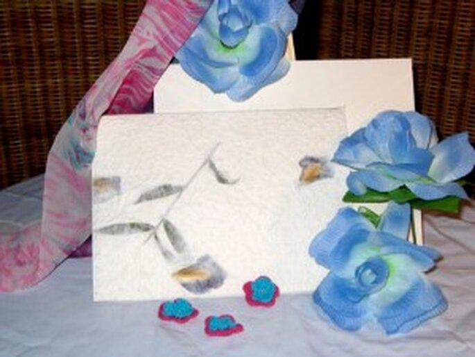 Invitación clásica sobre pasta de papel natural decorado con tallos de flor y pétalos azules.