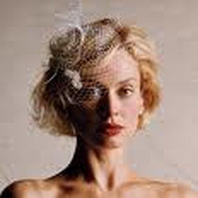 Tocado compuesto por redecilla, flores y plumas complementan perfecto este peinado suelto y corto y vestido palabra de honor