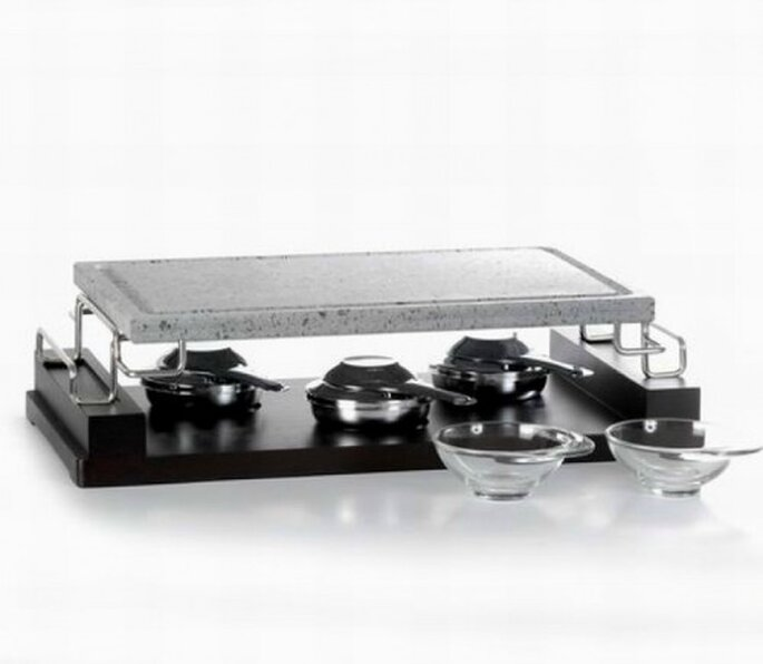 Set composto da 8 pezzi per preparare e consumare il cibo direttamente sulla tavola: una piastra con scanalatura in pietra lavica, supporto in acciaio inox, vassoio in legno,tre fornelli e due ciotole in vetro per salse o condimenti.  E' sufficiente pre-riscaldare la piastra, porla sul suo supporto in acciaio e introdurre al di sotto i tre fornelli accesi che provvederanno a mantenere la giusta temperatura per la cottura. E' altresì possibile usarla portandola direttamente in tavola con i cibi già cotti. Foto: http://www.pastorinocasa.com/it