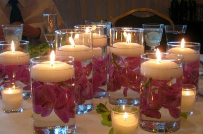 Candele galleggianti inserite in vasi di vetro con fiori. Foto www.matrimonio.pourfemme.it