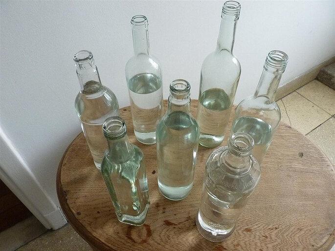 Botellas de formas diferentes para hacer floreros y decorar las mesas en tu boda. Foto: Zankyou Magazine