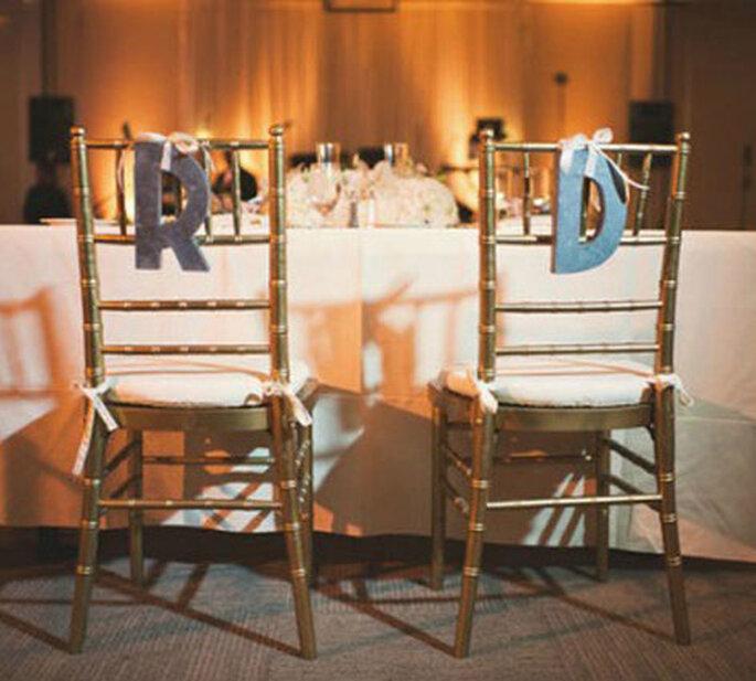 Iniciales de los novios recortadas y anudadas a las sillas con cintas. Foto: Style me pretty