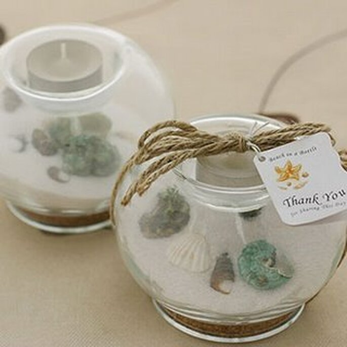Bougie constituée d'un récipient en verre rempli de sable et de coquillages