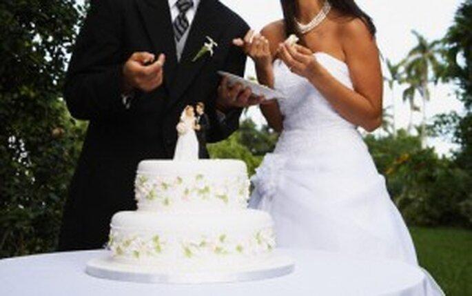 Los novios frente al pastel de bodas
