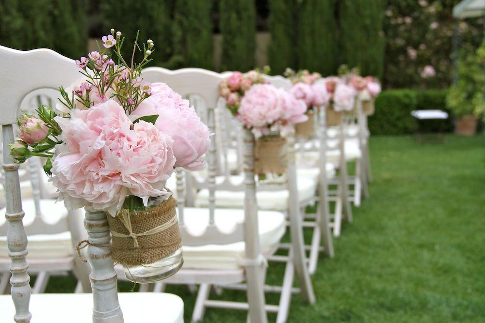 frascos con peonías para las sillas de la ceremonia