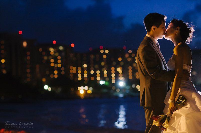 retrato de los novios en Punta Cancun con luz de flash por detrás y con bokeh usando los edificios del fondo