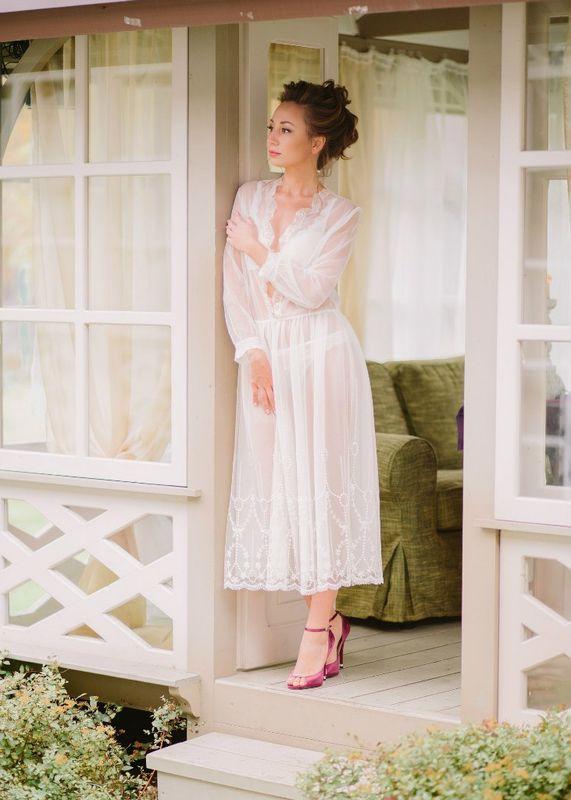 Будуарное платье Анжелина обладает по-королевски роскошным видом. Здесь нет вычурных деталей, каждый элемент одеяния очень прост, но вместе с тем изящен. Легкая кружевная ткань молочного цвета полупрозрачна. Она не скрывает красоту тела, однако и не выставляет ее напоказ. Отделка рукавов, по низу и по линии груди привлекает особое внимание.   Одна из главных особенностей модели - ее глубокий вырез до линии талии. Он позволяет показать все очарование и совершенство женской груди. Это шикарное будуарное платье придется по вкусу не только невестам, но и всем, кто любит прекрасные вещи.