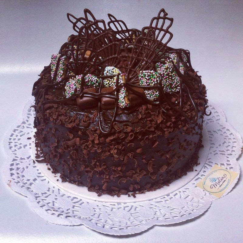 Torta fun (biscochuelo de chocolate relleno de fudge, cubierto con fudge y decorado con snickers, dona pepa, trufas y chocolate)