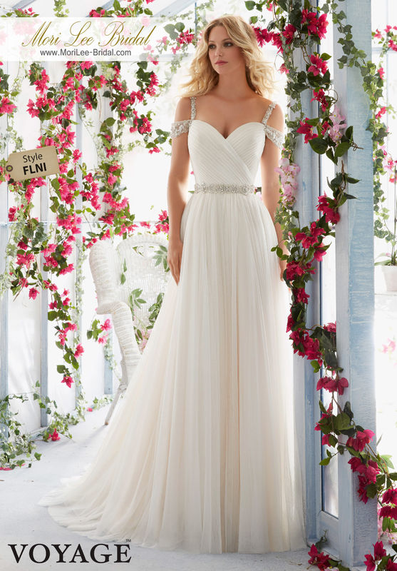 Dress Style FLNI  CRYSTAL BEADED EMBROIDERED STRAPS ON COLD SHOULDER, ASYMMETRICALLY DRAPED BODICE WITH SOFT TULLE SKIRT AND BEADED WAISTBAND  Colors available: White/Silver, Ivory/Silver, Light Gold/Silver.