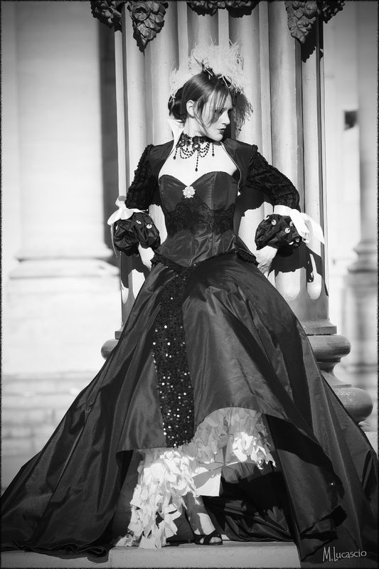 BAROQUE Cet ensemble de mariage original est  composé d'un bustier corseté en taffetas de soie noire rehaussé d'une broderie perlée, bordé d'une mousseline agrémentée de sequins noirs. La jupe est supportée par un jupon à crinoline bordé de taffetas de soie blanche  pliée en origami et découpée ensuite,  offre une ampleur princière. Le cache épaule à col montant, orné d'une croix baroque sur le dos propose un bas de manche » ballon » avec des sequins nacrés… Magie Noire fut portée également par Miss France 2009. Une charme… inattendu pour une tenue de mariée,  résolument ancré dans la contradiction du traditionnel…Modèle réalisé en collaboration avec Lolita  pour LEA MADELEINE Couture et selon inspirations et création de LEA MADELEINE Couture. Le photographe est Marc Lucascio