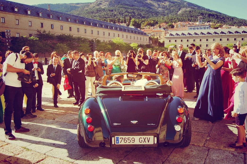 Los invitados rodean el coche a la salida de la ceremonia.