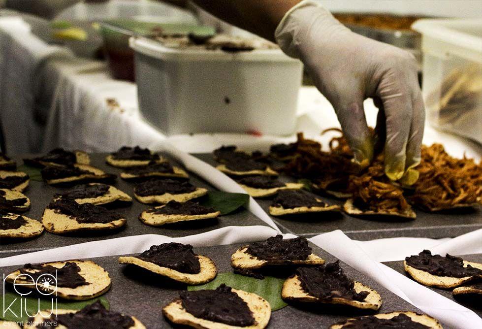 Montaje de tostaditas de cochinita pibil, frijoles negros, salsa Xni-Pec