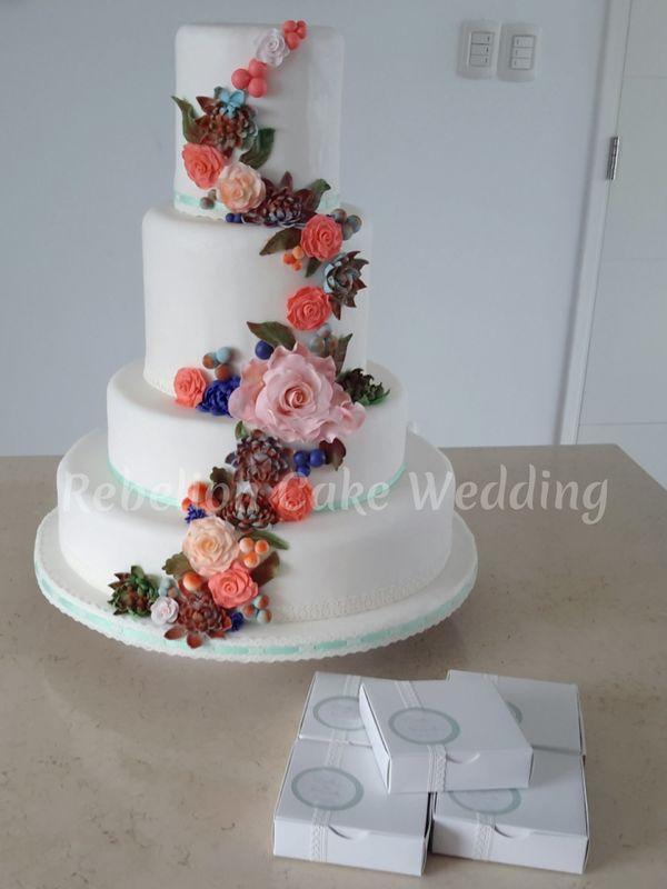 Torta y cajitas para torta, manteniendo el tema de la decoración del evento y los colores de los novios.