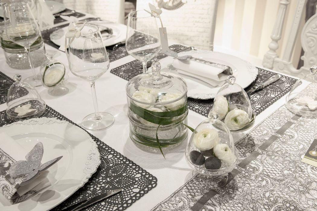 Une jolie table de mariage avec ses sets de tables gris dentelle, ses papillons prêts à s'envoler, ses décorations en verre pouvant accueillir vos fleurs blanches naturelles, ses bougies ...