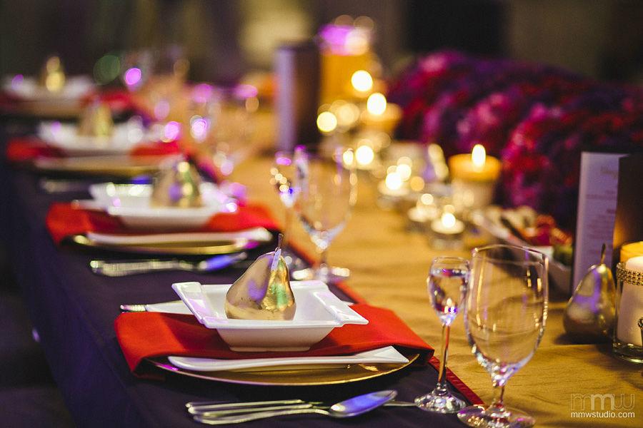 Dekoracje stołów: złoto, czerwień i fiolet.