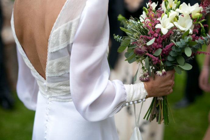 Detalle de espalda abierta con escote en V.  Vestido con cuerpo de valencienne y plumeti con falda de muselina de Cristina Piña.