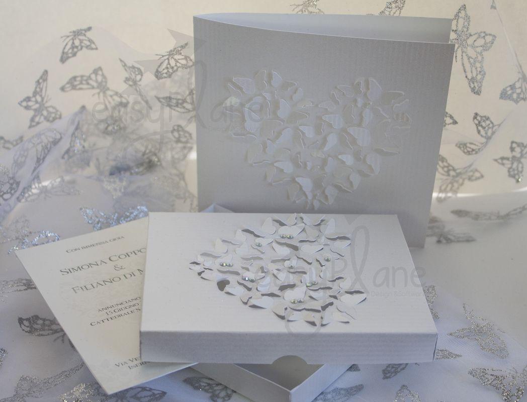 Un elegante volo di farfalle per la partecipazione in scatola e la cover per il libretto della cerimonia.