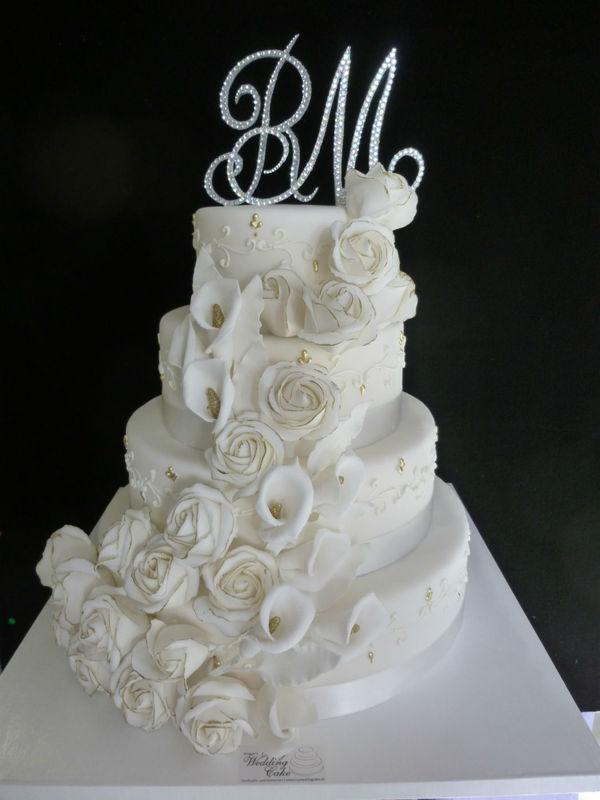 Wunderschöne Hochzeitstorte in weiss mit vergoldeten Rosen und Callas. Topper mit Strasssteinen. Foto:Bruggers My Weddingcake.ch