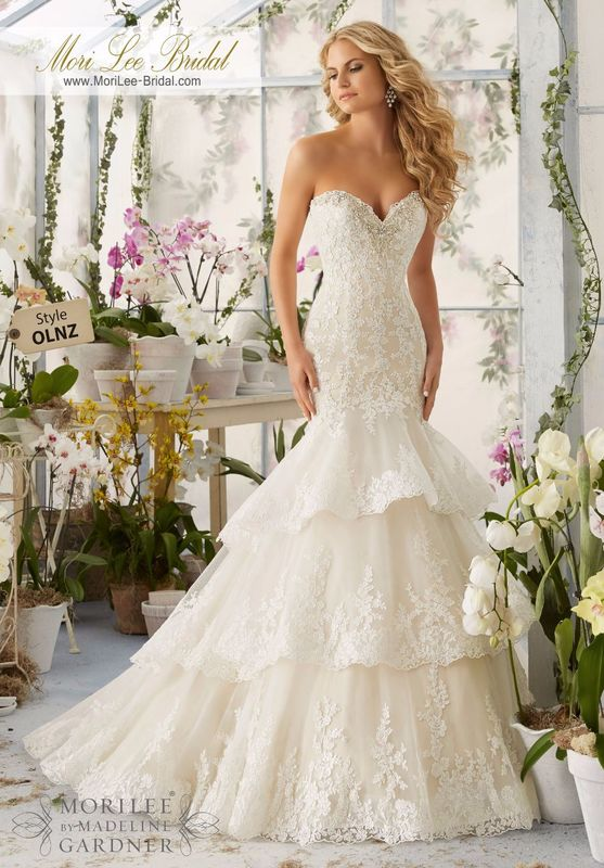 """Dress Style OLNZ Crystal Moonstone Beading Meets Alencon Lace Appliques And Scalloped Edging Onto The Tiered Tulle Gown  Removable Spaghetti Straps. Available in Three Lengths: 55"""", 58"""", 61"""". Colors available: White/Silver, Ivory/Silver, Light Gold/Silver"""