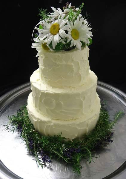 Merhstöckige Hochzeitstorte mit echtem Blumenstrauß oben in die Torte eingesetzt.  Mit einem Kranz von Blumen unten um die Torte herum.