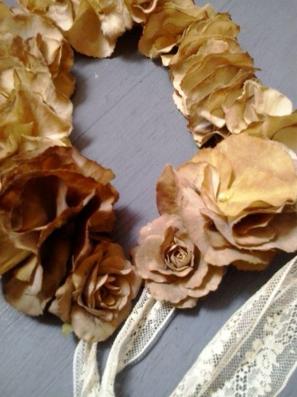 Corona beige con terminaciones de rosas doradas.
