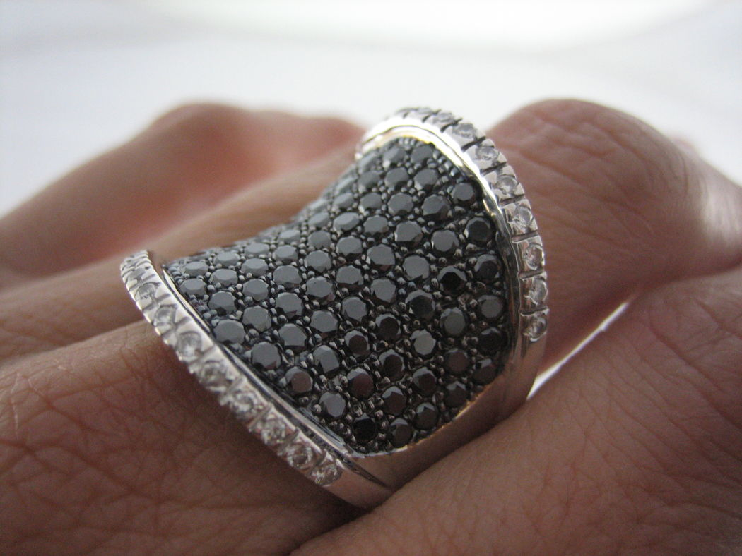 Quieres un anillo super trendy que seguirás usando mucho después de la boda? Atrévete con este modelo en oro blanco con cuajado de diamantes negros y blancos.