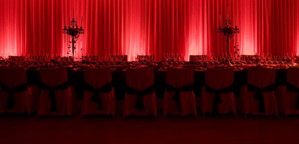 Ambientación con iluminación en las cortinas de fondo y candelabros con centros florales.  http://lafloreria.net