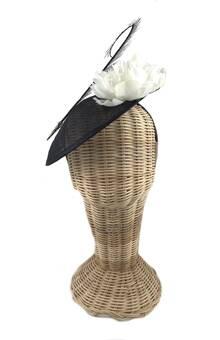 Tocado de sinamay en color negro con diadema para su sujección. Lleva dos flores de tela en color blanco y pluma rizada. Alquiler o compra.