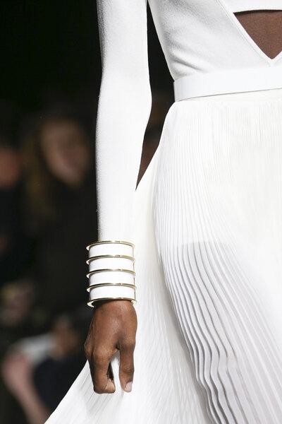 Detalle de brazalete con vestido de falda plisada todo en blanco.