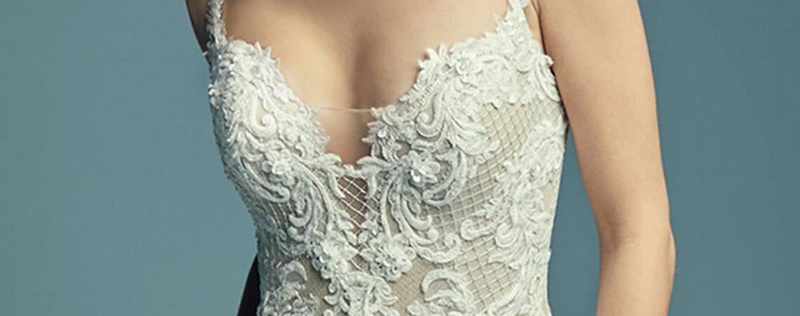 """<a href=""""https://www.maggiesottero.com/maggie-sottero/abbie/11450"""">Maggie Sottero</a>  Elegante vestido de novia entallado con escote corazón y motivos de encaje bordados. ¡Muy favorecedor para la silueta femenina!"""