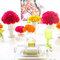 Pięknie przybrany stół weselny: kompozycja florystyczna z żółtych, pomarańczowych i różowych kwiatów, Foto: Cathrin D'Entremont