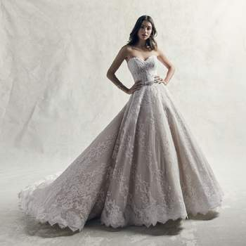Motivos románticos de encaje se deslizan sobre el tul de este impresionante vestido de novia de corte princesa. Todo un vestido de gala con escote corazón sin tirantes y dobladillo.
