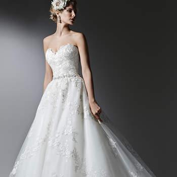 """Renda romântica e camadas de tule cintilante, compõem este vestido de noiva, acentuado com um cinto delicado de cristal Swarovski e decote de coração. Acabamento com espartilho interno e botões de cristal sobre zíper. <a href=""""https://www.maggiesottero.com/sottero-and-midgley/alandra/9571"""" target=""""_blank"""">Sottero and Midgley</a>"""