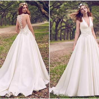 "Beaded lace motifs and Swarovski crystals adorn the waistline and illusion open back in this Gala Satin wedding dress. A deep V-neckline completes this elegant ballgown. Finished with crystal buttons and zipper closure.  <a href=""https://www.maggiesottero.com/maggie-sottero/corianne/11164?utm_source=zankyou&amp;utm_medium=gowngallery"" target=""_blank"">Maggie Sottero</a>"