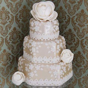 Tarta cubierta en fondant color marfil perlado con aplicaciones y flores de azúcar blancas texturizadas con un maravilloso encaje valenciano antiguo.