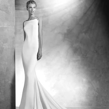 Vestido de noiva em crepe, estilo sereia. Corpo com decote em barco decorado com pedraria nos ombros. Costas com decote quadrado bordado com aplicações de pedraria.