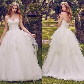 """Los adornos de encaje floral en 3D acentúan el escote y el escote corazón en este vestido de novia de princesa, ligeramente en cascada en una falda de tul en capas. Terminado con botones de cristal sobre la cremallera y el cierre interno del corsé.  <a href=""""https://www.maggiesottero.com/maggie-sottero/maura/11177?utm_source=zankyou&amp;utm_medium=gowngallery"""" target=""""_blank"""">Maggie Sottero</a>"""
