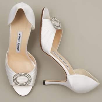 Escarpins blancs Manolo Blahnik ouverts avec une boucle brillante à l'avant de la chaussure : très chic. - Source : manoloblahnik.com