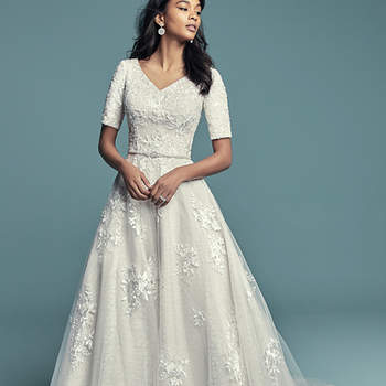 "<a href=""https://www.maggiesottero.com/maggie-sottero/meryl-marie/11497"">Maggie Sottero</a>  This vintage-inspired modest wedding dress features lace appliqués over whimsical layers of textured tulle and Chic Organza. Featuring a V-neckline and quarter sleeves. Swarovski crystals and beading add shimmer and ethereal texture. Finished with covered buttons over zipper and inner elastic closure. Detachable beaded belt featuring Swarovski crystals sold separately, BB7MS339MC."